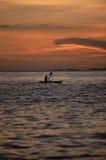 划皮船的人员海运剪影日落 免版税库存图片