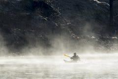 划皮船通过在岸附近的薄雾 免版税图库摄影