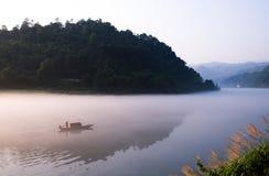 划船和渔在黎明 免版税库存照片