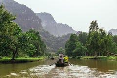 划船妇女行有游人河的有植物和树的和山的一条小船在的Trang的背景中 免版税库存图片