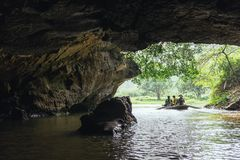 划船妇女行有游人的一条小船在洞里面的河的与树在背景中在的Trang洞穴在Ninh Binh 图库摄影