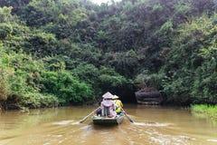 划船妇女行有游人的一条小船有洞入口的河的在的Trang的背景中洞穴在Ninh Binh,越南 免版税库存图片