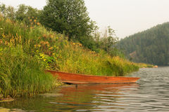 划艇在绿草的铁红色 免版税库存图片