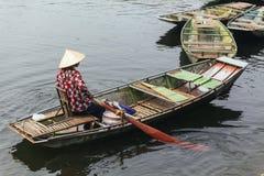 划艇妇女佩带红色和白色上色衬衣、圆锥形帽子和坐在有桨的一条小船的嘴面具在河 免版税库存照片