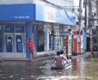 划艇的两个人通过一条被充斥的街道的一家TMB银行在Rangsit,泰国,在2011年10月 图库摄影