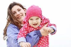 系列愉快的纵向 笑的面孔,拿着可爱的儿童女婴的母亲微笑和拥抱 户外妈妈和女儿 免版税库存图片