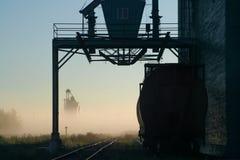 列车车箱由一个电梯休息在一个有雾的秋天早晨,等待天开始 剪影场面 库存图片