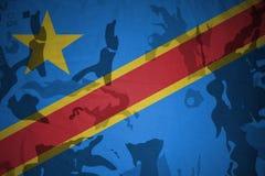 刚果民主共和国的旗子卡其色的纹理的 装甲攻击机体关闭概念标志绿色m4a1军用步枪s射击了数据条工作室作战u 免版税库存照片