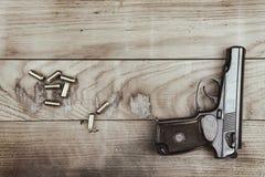 创伤手枪用子弹和弹药筒木表面上,葡萄酒作用 免版税库存照片