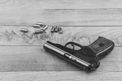 创伤木表面上的手枪用子弹和弹药筒,黑白 图库摄影