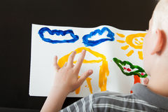 创造一个五颜六色的手指画法的年轻男孩 免版税图库摄影