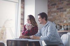 创造在便携式计算机上的年轻夫妇家庭预算 库存图片