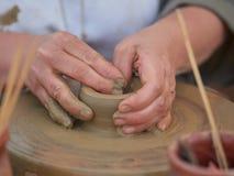 创造在横式转盘的女性陶瓷工一个碗 免版税库存图片