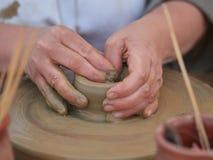 创造在横式转盘的女性陶瓷工一个碗 免版税库存照片