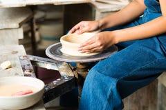 创造在转动的轮子的陶瓷工黏土碗 免版税库存图片