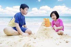 创造在海滩的两个孩子一座城堡 库存照片