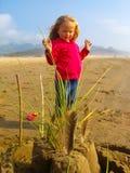 创造在晴朗的海滩的小女孩一个沙堡 免版税库存照片