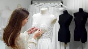 创造婚礼礼服的女孩的画象由专属命令缝合的织品和假钻石在礼服在a穿戴了 股票视频
