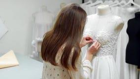 创造婚礼礼服的女孩的画象由专属命令缝合的织品和假钻石在礼服在a穿戴了 股票录像