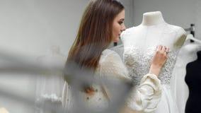 创造婚礼礼服的女孩的画象由专属命令缝合的织品和假钻石在礼服在a穿戴了 影视素材