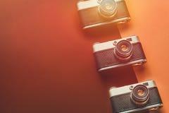 创造性减速火箭的技术概念 在红色和橙色背景,顶视图的影片照相机 库存图片