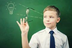 创造性和聪明的男小学生有一个想法在黑板 免版税图库摄影