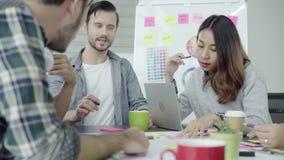 创造性的专家聚集了在会议桌上为讨论新的成功的起始的项目的重要问题 股票录像
