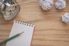 创造性的事务和想法概念:在有白色的笔记本上把放的使用的绿色铅笔弄皱了在木桌上把放的纸球 免版税图库摄影