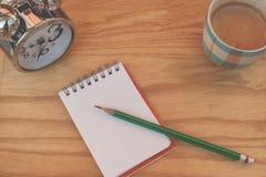 创造性的事务和想法概念:在有白色的笔记本上把放的使用的绿色铅笔弄皱了在木桌上把放的纸球 免版税库存照片