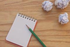 创造性的事务和想法概念:在有白色的笔记本上把放的使用的绿色铅笔弄皱了在木桌上把放的纸球 库存照片