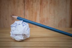 创造性的事务和想法概念:有白色的使用的铅笔弄皱了在木地板上把放的纸球 库存图片