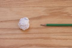 创造性的事务和想法概念:有白色的使用的铅笔弄皱了在木地板上把放的纸球 图库摄影