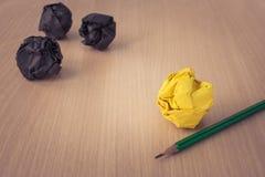 创造性的事务和想法概念:有黄色的使用的铅笔弄皱了在木地板上把放的纸球,并且黑色弄皱了纸球 免版税库存图片