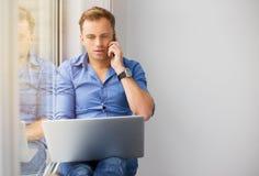 年轻创造性的人与计算机一起使用,当谈话在电话时 库存图片