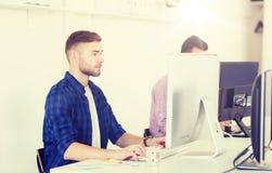 创造性的人或学生有计算机的在办公室 库存照片