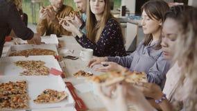 年轻创造性的企业队一起有膳食 吃薄饼的混合的族种人在现代办公室,享用食物