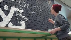 创造性的做白色设计的画家年轻女性画家在咖啡店的黑砖墙 股票视频
