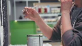 创造性的做白色设计的画家年轻女性画家在咖啡店的黑砖墙 影视素材