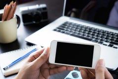创造性的办公室拿着一个空白的智能手机 库存图片