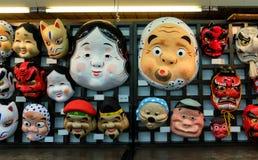 创造性的古老纸面具的各种各样的类型在垂悬在木墙壁上的传统事件的日本在市场上出售的 免版税图库摄影