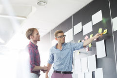 创造性的商人谈论在墙壁上的稠粘的纸在办公室 免版税库存图片