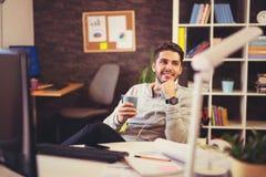 创造性的在书桌的商人听的音乐在办公室 图库摄影