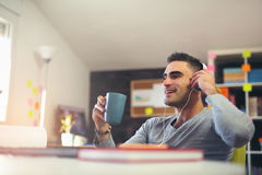 创造性的在书桌的商人听的音乐 免版税库存图片