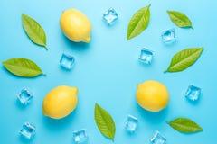 创造性的夏天构成用柠檬和冰块在蓝色背景 最小的饮料概念 图库摄影