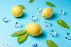 创造性的夏天构成用柠檬和冰块在蓝色背景 最小的饮料概念 免版税库存图片