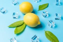 创造性的夏天构成用柠檬和冰块在蓝色背景 最小的饮料概念 免版税库存照片