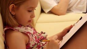 创造性的女孩图画侧视图在备忘录的,当在家时坐沙发 想象力的概念,创造 股票录像