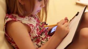 创造性的女孩图画侧视图在备忘录的,当在家时坐沙发 想象力的概念,创造 股票视频