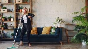 创造性的女孩是唱歌和跳舞与拖把在家事期间在有美丽的家具和植物的好的房子里 乐趣 股票视频