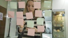 创造性的女实业家和人激发灵感会议的在现代玻璃办公室 使用不同的颜色贴纸 股票录像